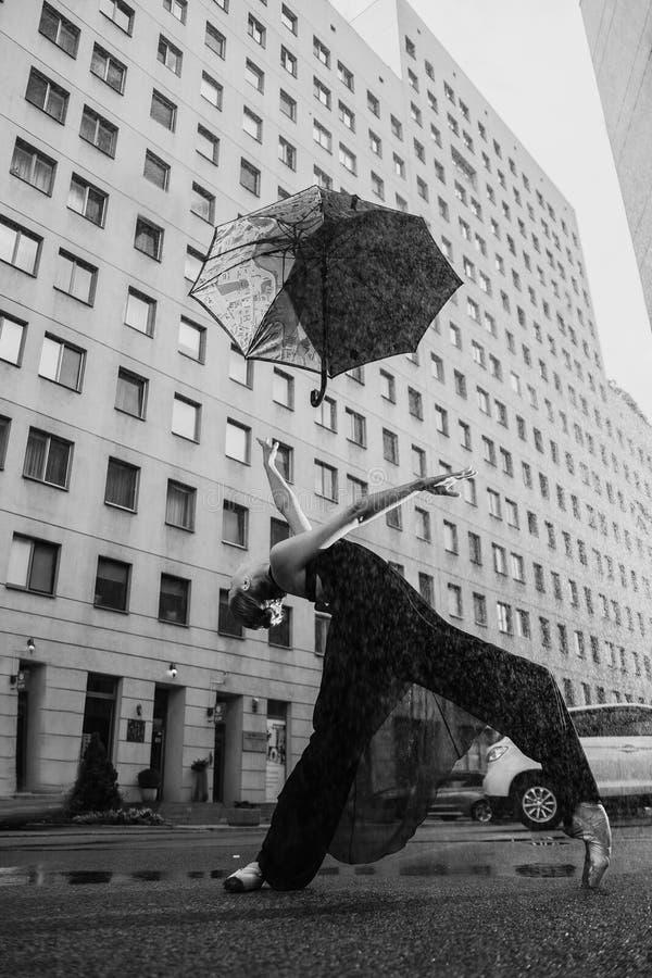 Ballerina con l'ombrello sulla via della città al di sotto delle gocce di acqua immagine stock