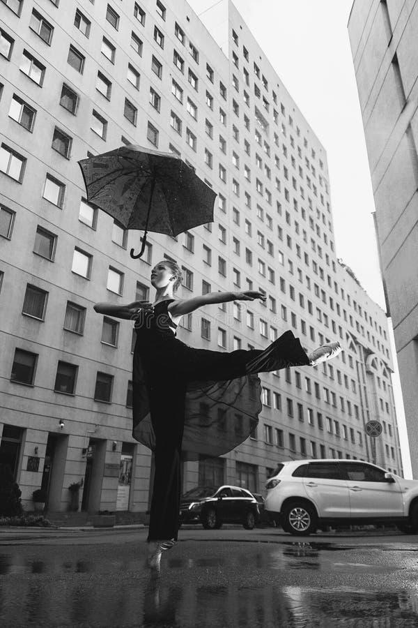 Ballerina con l'ombrello sulla via della città al di sotto delle gocce di acqua fotografie stock