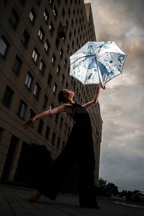 Ballerina con l'ombrello sulla via della città sul cielo e sul bui del fondo immagine stock