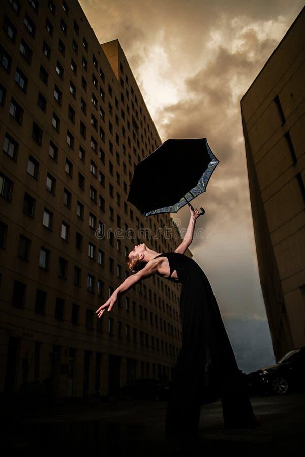 Ballerina con l'ombrello sulla via della città sul cielo e sul bui del fondo fotografia stock libera da diritti