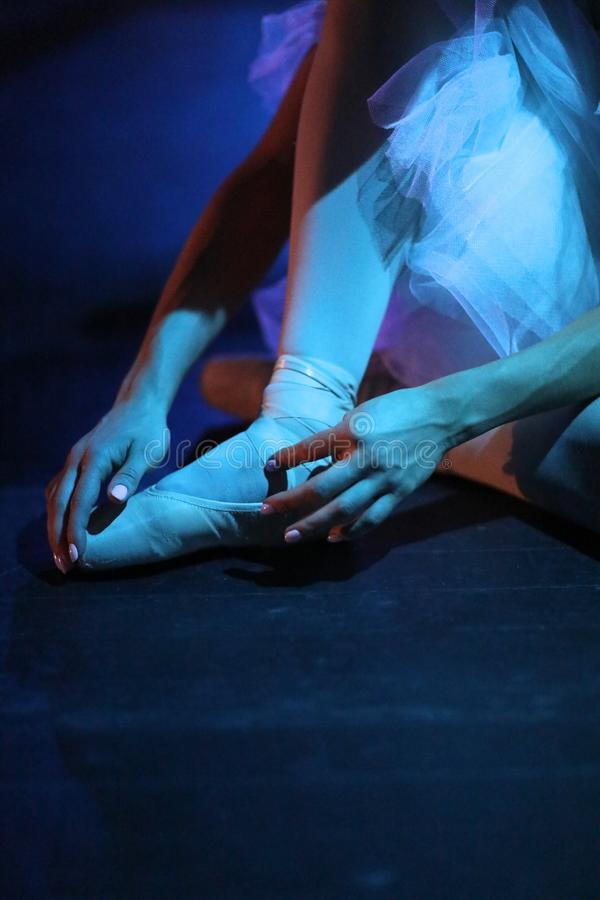 Ballerina puts on pointe shoes stock photography
