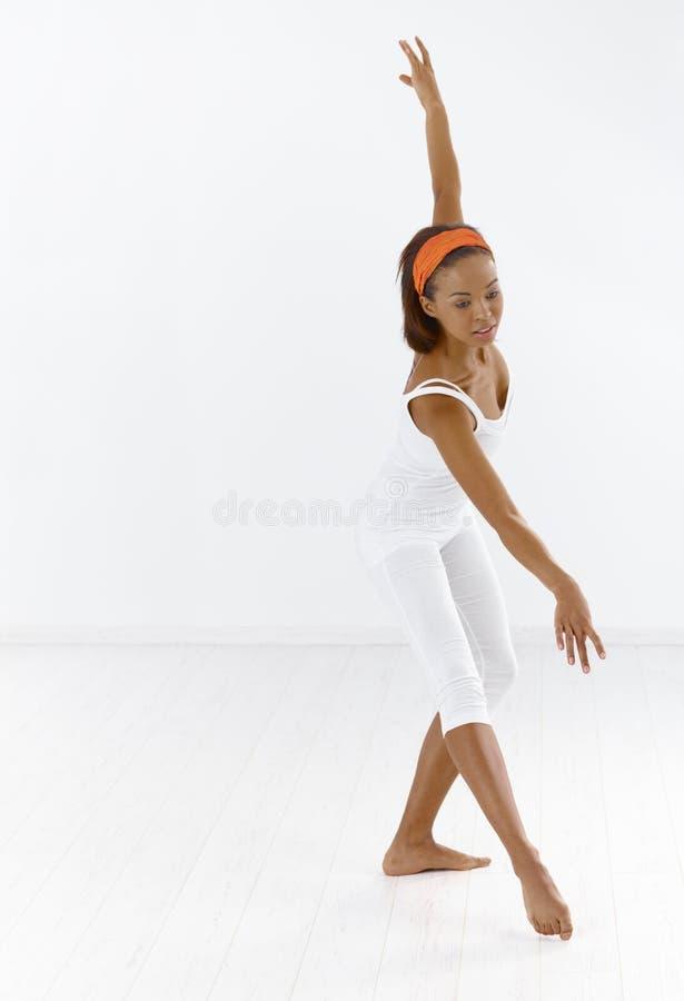 Ballerina dancing. Afro ballerina dancing in studio, concentrating royalty free stock photography