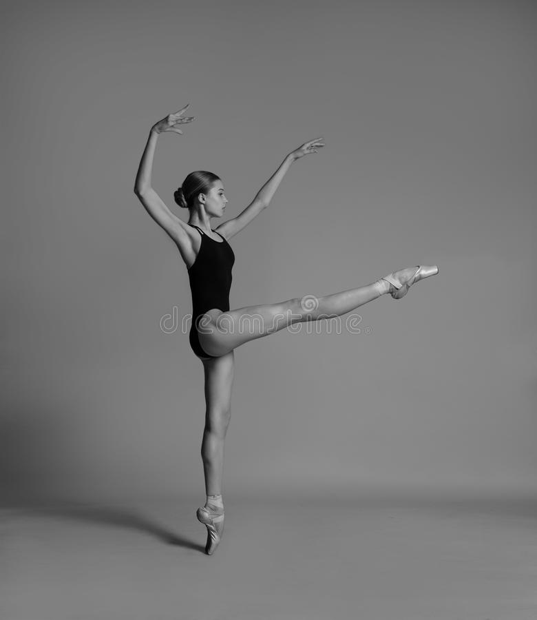 A ballerina is dancing in the studio. Ballerina is dancing in black leotard and pointe shoes. Shooting in the studio. Black and white photo stock image