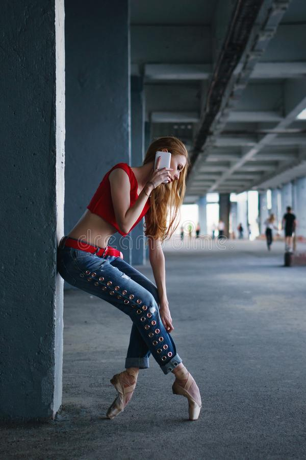 Ballerina dancing with a cell phone. Street performance. royalty free stock images