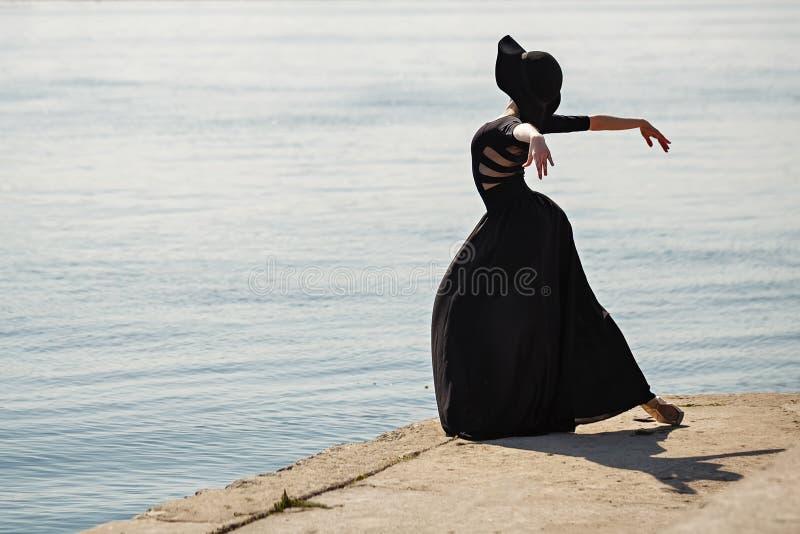 Ballerina dancing del vestito nero lungo e del cappello nel bello fotografie stock