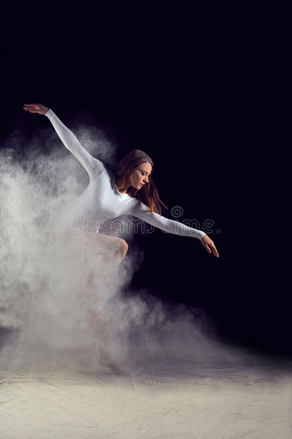 Ballerina dancing with flour on a black background royalty free stock photo