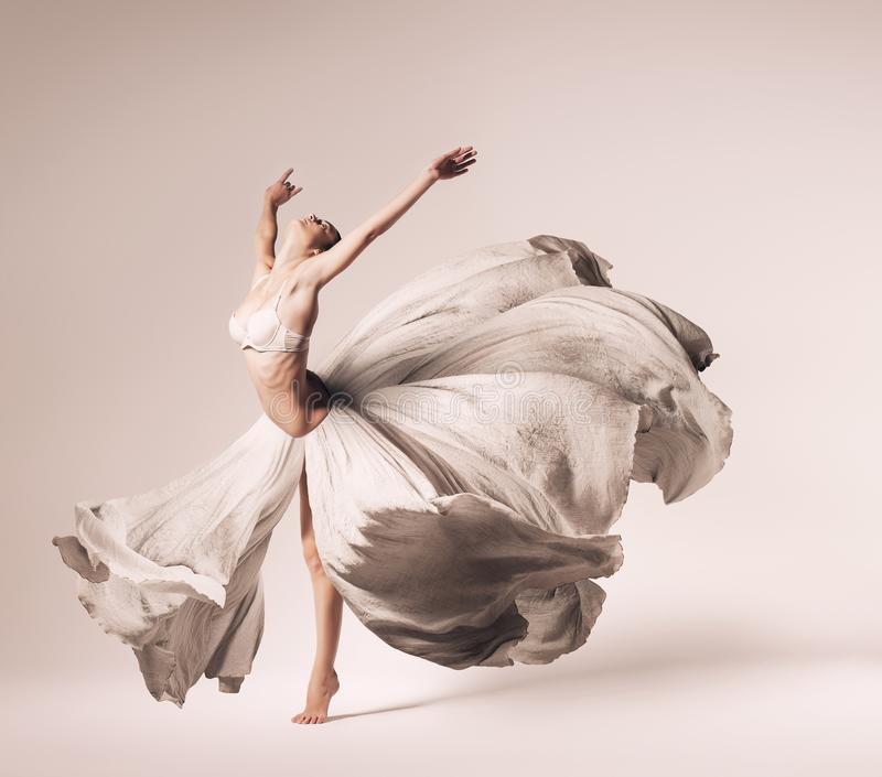 Ballerina dancing in flowing dress royalty free stock images
