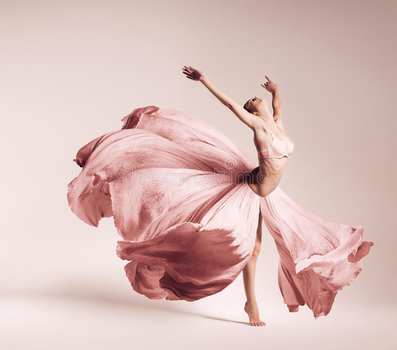 Ballerina dancing in flowing pink dress royalty free stock photography