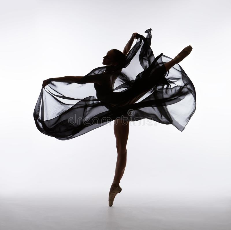 A ballerina is dancing with flying cloth. Ballerina is dancing with flying cloth in pointe shoes. Shooting in the studio. Color photo royalty free stock photo