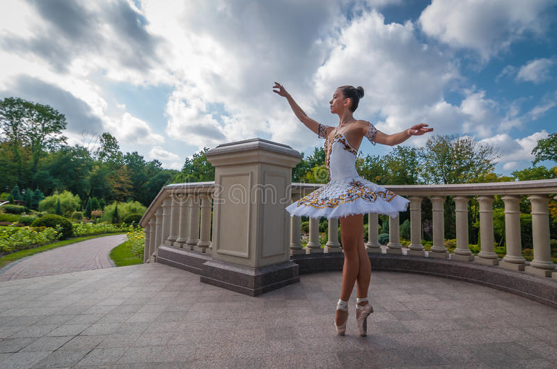 Ballerina dancing near columns, standing in pointe position. Outdoors, spring stock images