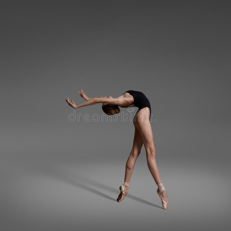 A ballerina is dancing in the studio. Ballerina is dancing in black leotard and pointe shoes. Shooting in the studio. Ballerina bends backwards stock photo