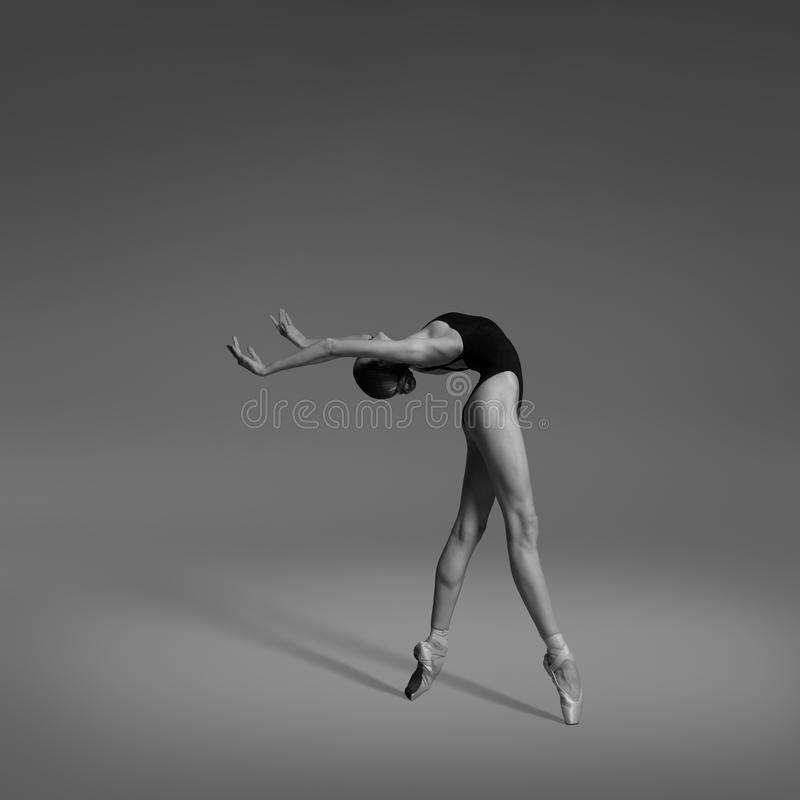 A ballerina is dancing in the studio. Ballerina is dancing in black leotard and pointe shoes. Shooting in the studio. Black and white photo. Ballerina bends royalty free stock images