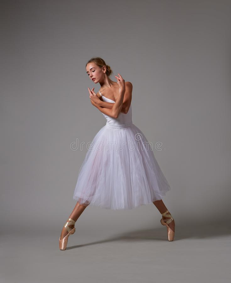 Ballerina dancing in white dress. Color photo. Ballerina dancing in white dress and pointe shoes. Color photo royalty free stock photos