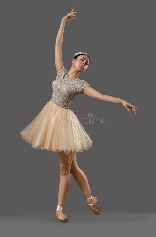 Ballerina in den beige Kleider- und Ballettschuhen, die in Studio tanzen stockbilder