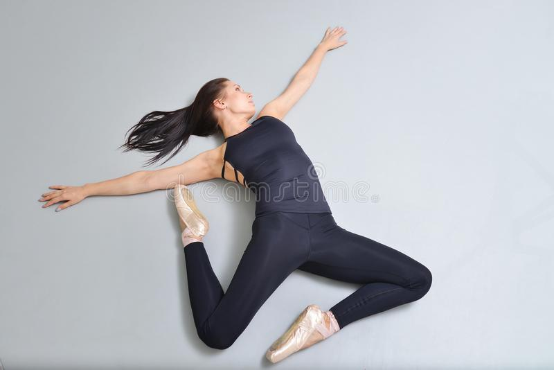 Ballerina der jungen Frau, die auf den Boden am Ballettstudio, Ansicht von oben liegt und ausdehnt Modellieren der Fliege oder de stockbild