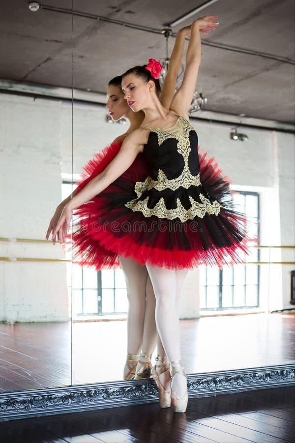 Ballerina di ripetizione nel corridoio Stanza bianca leggera, pavimento di legno, grandi specchi Ballerina riflessa nello specchi immagini stock libere da diritti