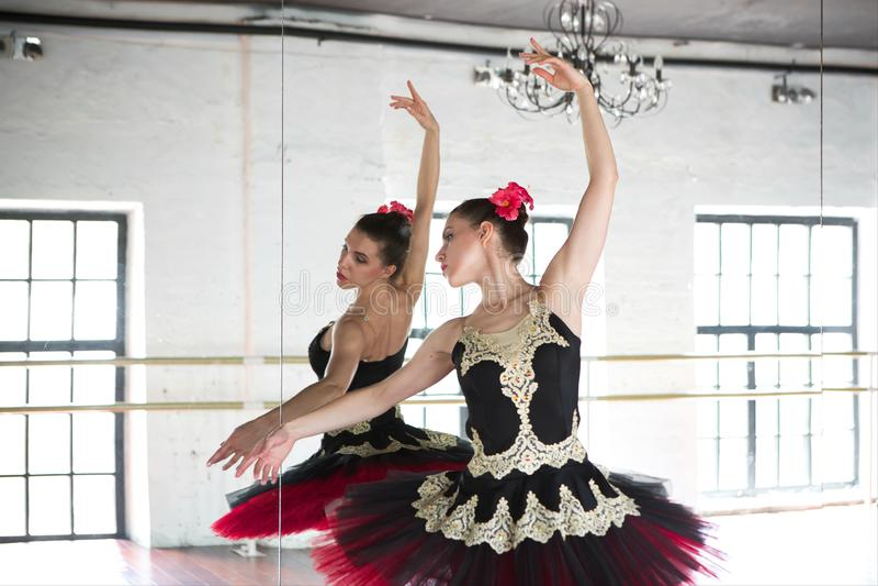 Ballerina di ripetizione nel corridoio Stanza bianca leggera, pavimento di legno, grandi specchi Ballerina riflessa nello specchi fotografia stock
