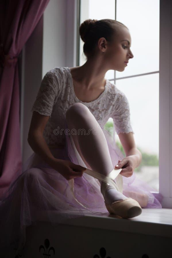 Ballerina, die auf Fensterbrett sitzt lizenzfreie stockfotografie