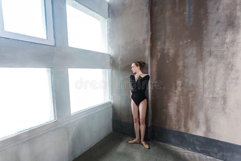 Ballerina die dichtbij venster, omhelzing zelf wachten en weg kijkend royalty-vrije stock foto