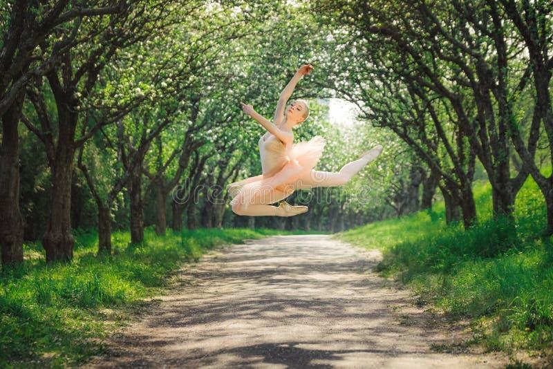 Ballerina, die draußen tanzt und hoch in die Luft springt stockfotografie