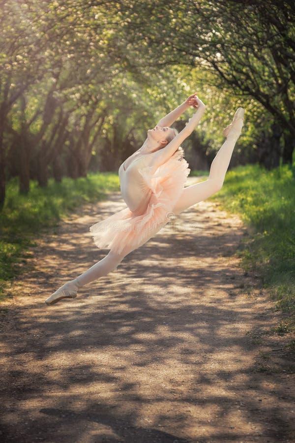 Ballerina, die draußen tanzt und hoch in die Luft springt stockfoto