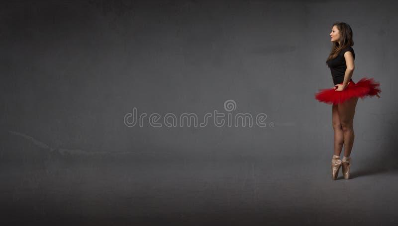 Ballerina, die ein leeres abastract Ballsaal schaut stockfotos