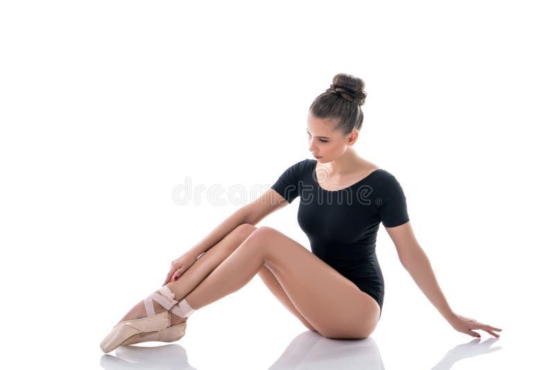 Ballerina die haar slanke benen in pointes bekijken stock afbeeldingen