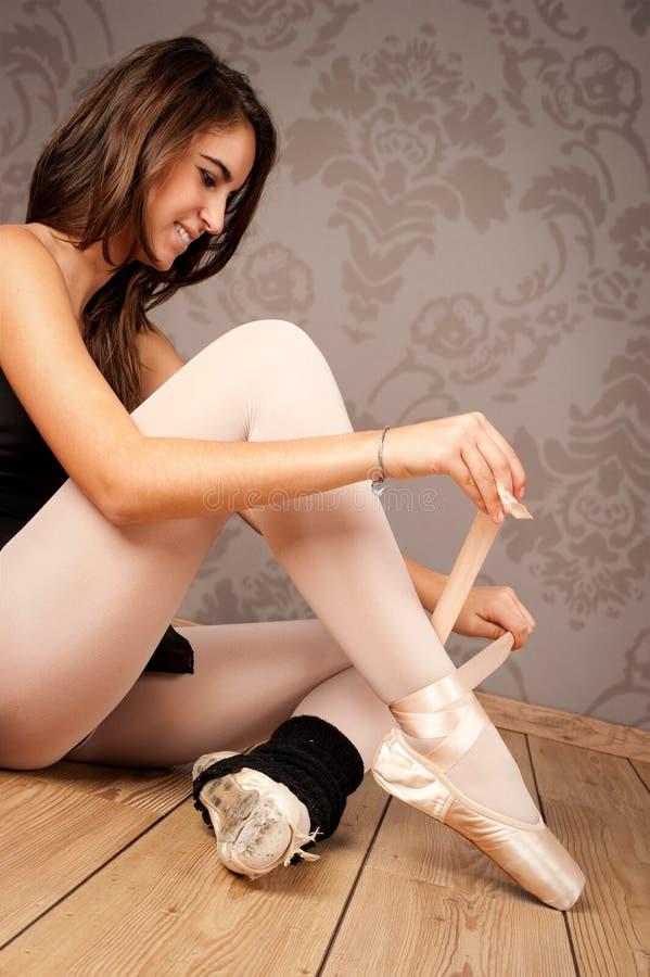 Ballerina, die ihre Ballettpantoffel bindet lizenzfreies stockfoto