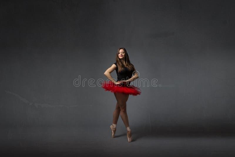 Ballerina, die mit rotem Ballettröckchen lächelt lizenzfreie stockfotos