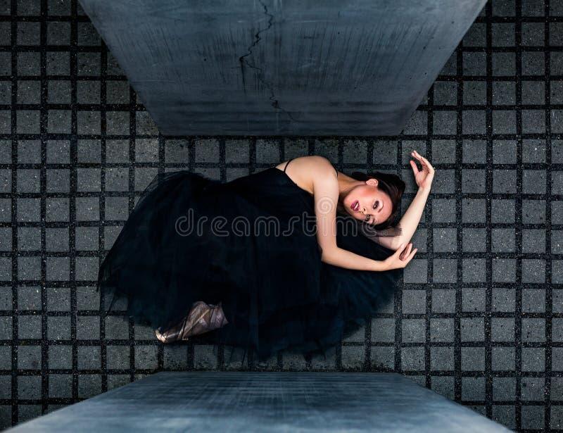 Ballerina die op grijze tegels tussen plakken liggen stock afbeeldingen