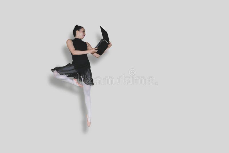 Ballerina, die Sprung mit Laptop auf Studio durchführt stockbilder