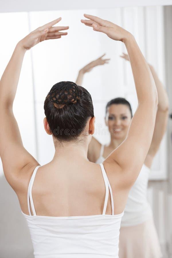 Ballerina die terwijl het Bekijken Spiegel praktizeren stock afbeeldingen
