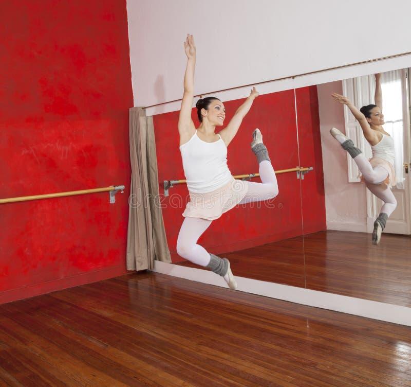 Ballerina die terwijl het Presteren in Dansstudio springen royalty-vrije stock fotografie