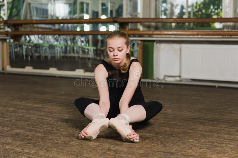 Ballerina die uitrekkende oefeningen doen stock afbeeldingen