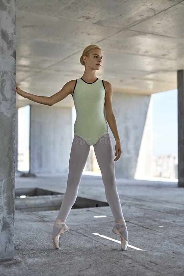 Ballerina, die an unfertigem Gebäude aufwirft stockfoto