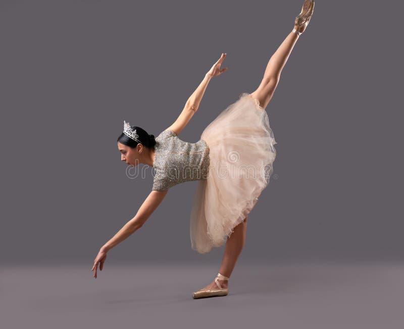 Ballerina, die unten verbiegt und ein Bein oben im Studio anhebt stockbilder