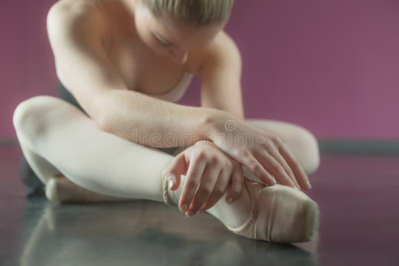 Ballerina, die vorwärts sitzt und verbiegt stockfoto