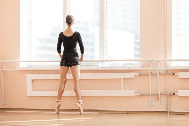 Ballerina die zich op poite bij staaf in balletklasse bevinden stock afbeelding