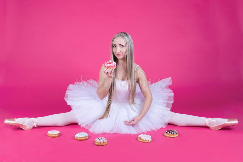 Ballerina doing a split in tutu skirt eating a donut royalty free stock image