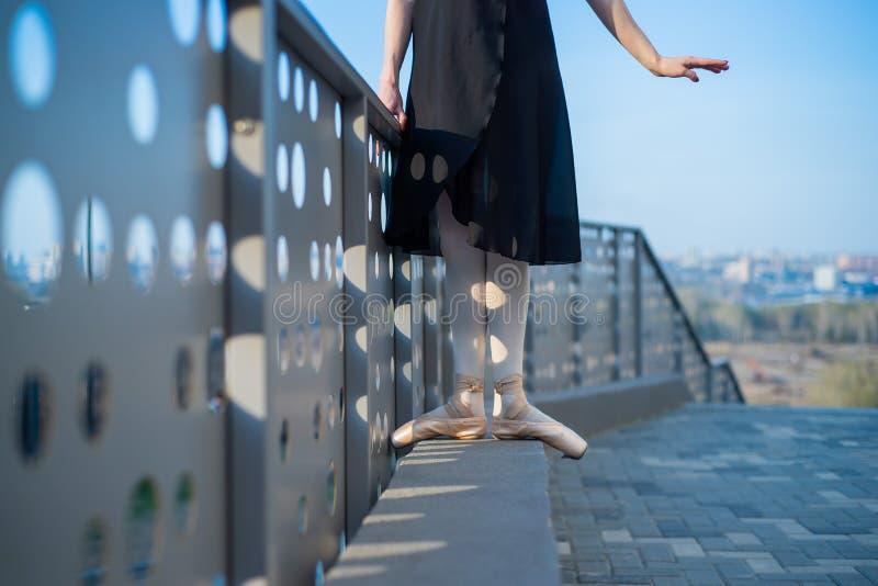 Ballerina en ballet jambes en chaussures et tutu noir dansant près de la clôture Belle jeune femme en robe noire et danse à point images stock