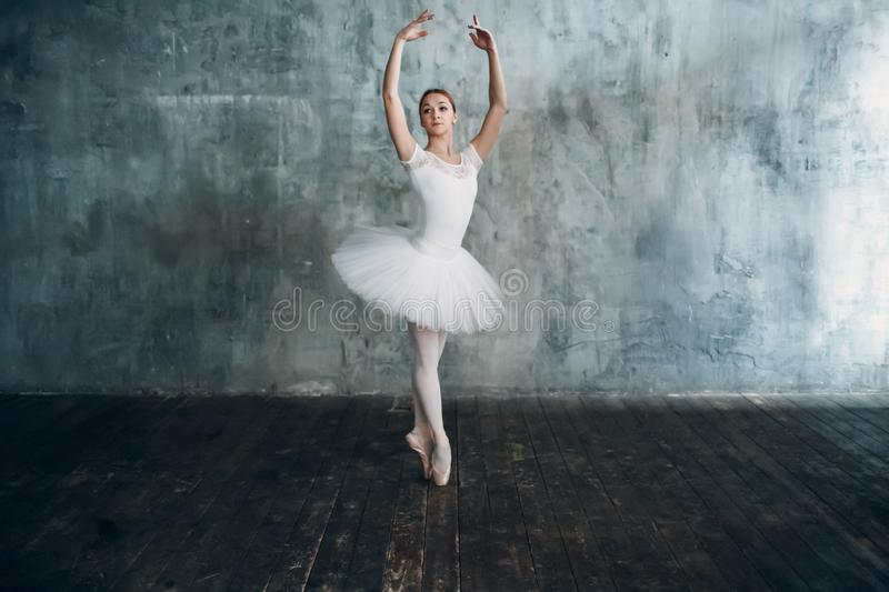 Ballerina female. Young beautiful woman ballet dancer, dressed in professional outfit, pointe shoes and white tutu. royalty free stock photo