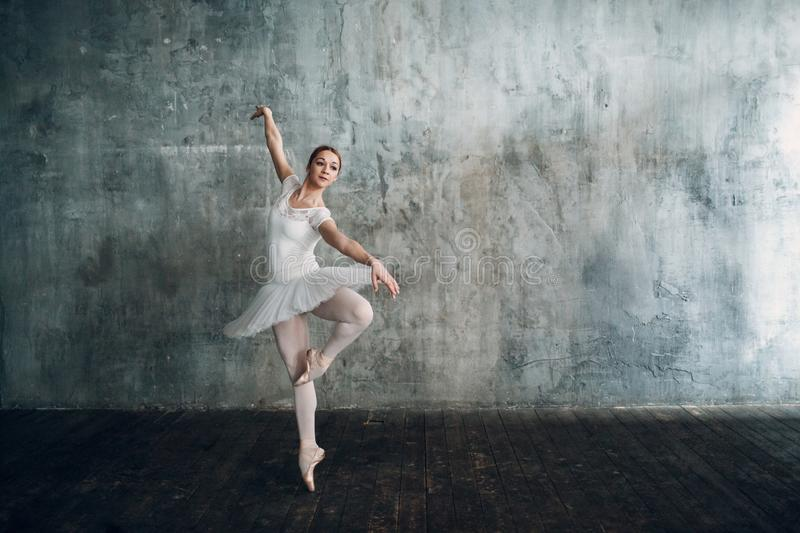 Ballerina female. Young beautiful woman ballet dancer, dressed in professional outfit, pointe shoes and white tutu. royalty free stock image