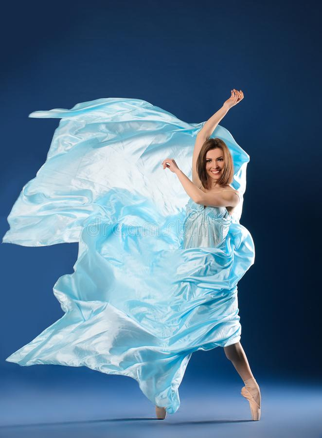 Ballerina in flying blue dress royalty free stock images