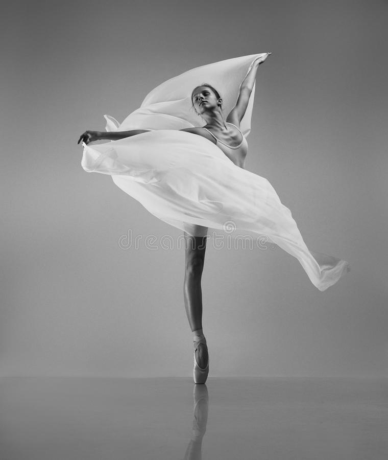 Ballerina with flying cloth. The professional ballerina in pointe shoes with flying white cloth stock photography