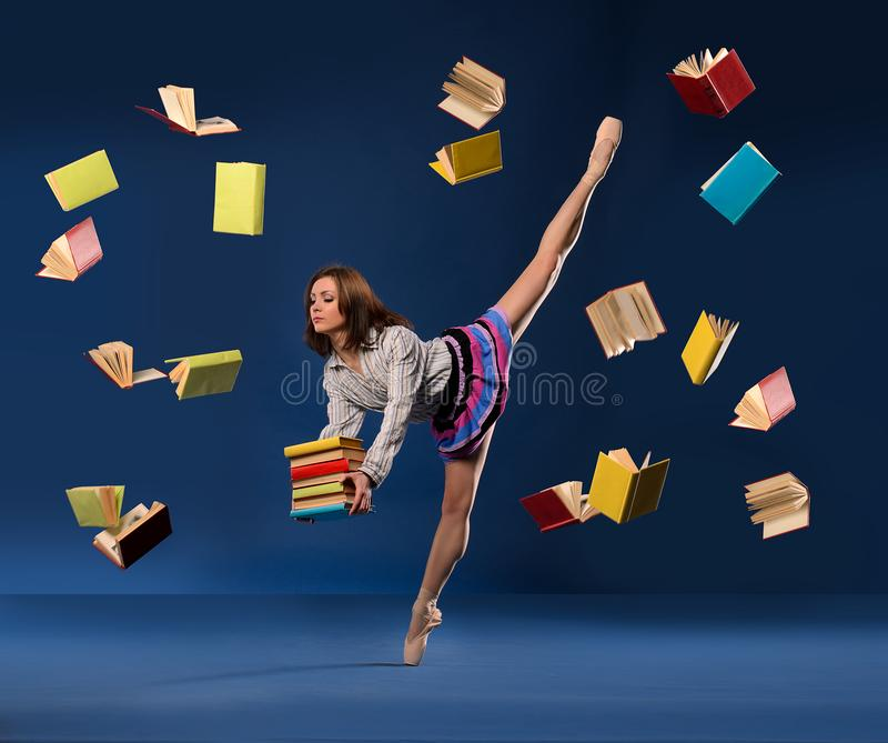 Ballerina in form of schoolgirl with pile books stock photography