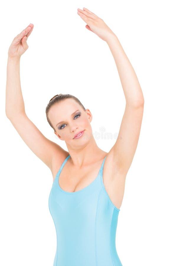 Ballerina graziosa sorridente che posa con le sue armi alzate fotografia stock