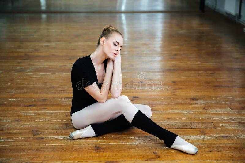 Ballerina het ontspannen op de vloer stock foto