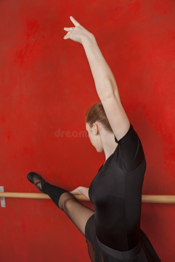 Ballerina het Uitrekken zich in Barre In Training Studio stock foto