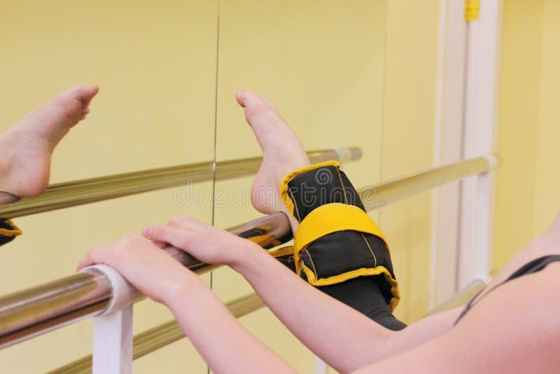 Ballerina het uitrekken zich bij de staaf stock foto's