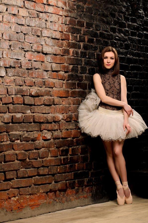 Ballerina i ballerinakjol nära tegelstenväggen arkivfoto